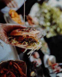 Burger wird in Hand gehalten